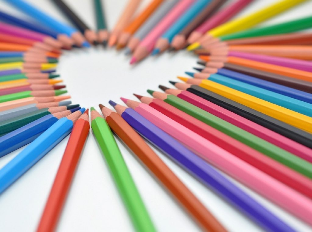 A rainbow of colored pencils arranged to form a heart